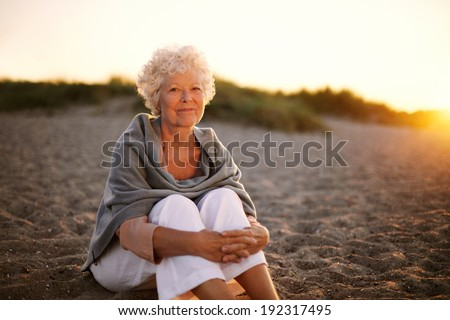 Portrait of happy old woman sitting on the beach. Retired caucasian lady relaxing outdoors - stock photo