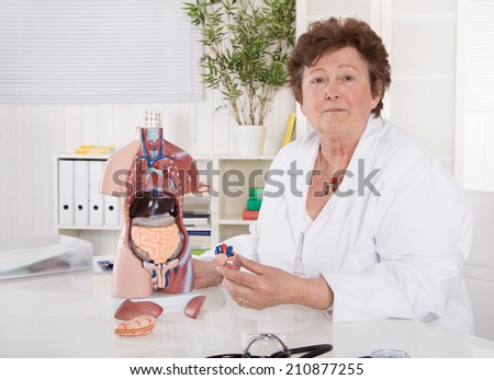 Portrait of happy older senior doctor or professor explaining the human body with a torso. - stock photo