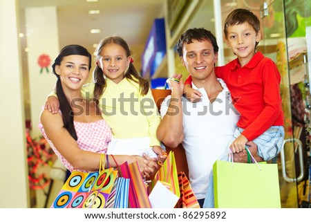 Portrait of happy parents and children with paperbags after shopping - stock photo