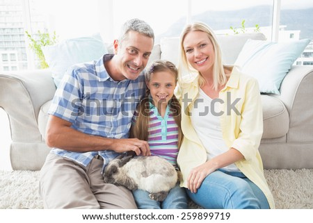 Portrait of happy parents and daughter with rabbit sitting in living room