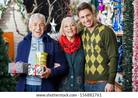 Portrait of happy parents and son with presents standing in Christmas store - stock photo