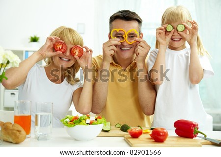 Portrait of happy parents and their daughter posing with vegetables in the kitchen - stock photo