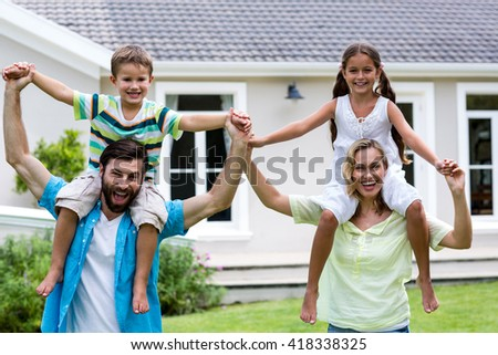 Portrait of happy parents carrying children on shoulder at yard