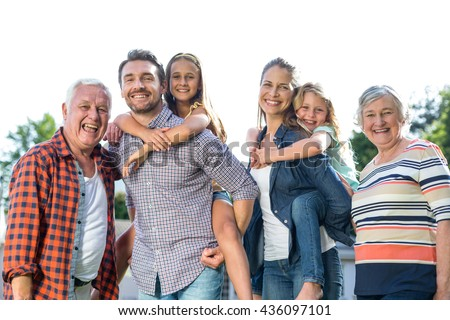 Portrait of happy parents carrying girls with grandparents standing in back yard - stock photo
