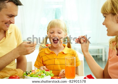 Portrait of happy parents feeding their daughter with salad in the kitchen - stock photo