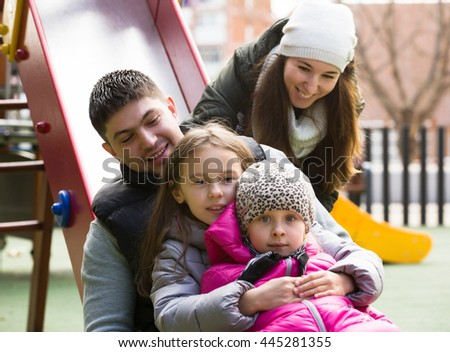 Portrait of happy parents helping little kids on slide in autumn day. Focus on man - stock photo