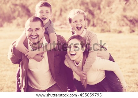 Portrait of happy parents holding two kids on the shoulders outdoors. Focus on boy - stock photo