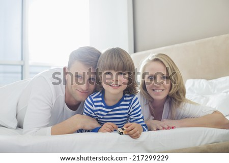 Portrait of happy parents lying with son in bed