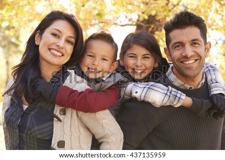 Portrait of happy parents piggybacking kids outdoors - stock photo