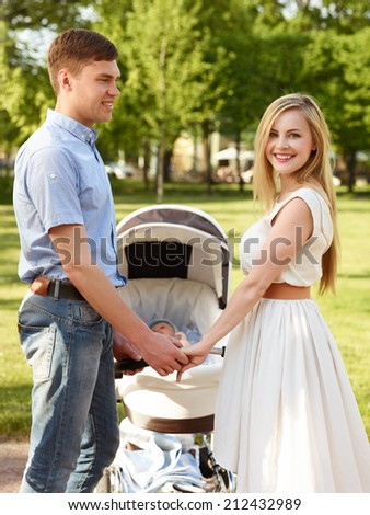 Portrait Of Happy Parents With Baby In Stroller At Park - stock photo