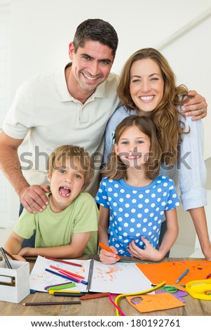 Portrait of happy parents with children drawing at table - stock photo