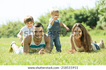 Portrait of happy parents with children in grass at park