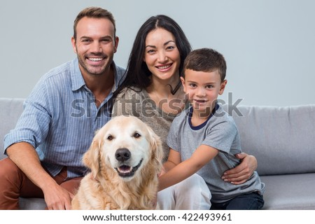 Portrait of happy parents with son and pet in living room - stock photo