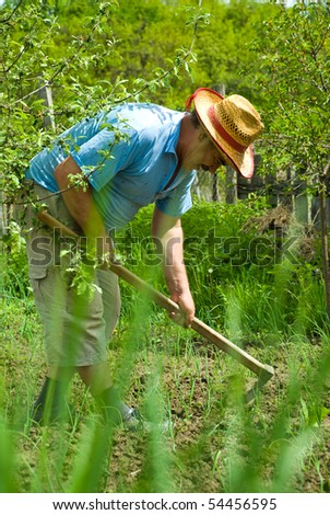 Portrait of happy peasant digging in the garden soil with spring onions at country - stock photo