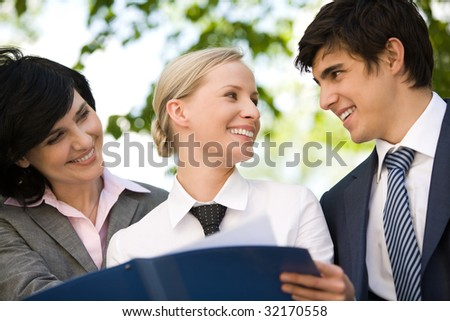 Portrait of happy people discussing new working plan outside at summer