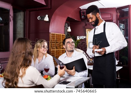 Portrait of happy people in middle class restaurant and black waiter