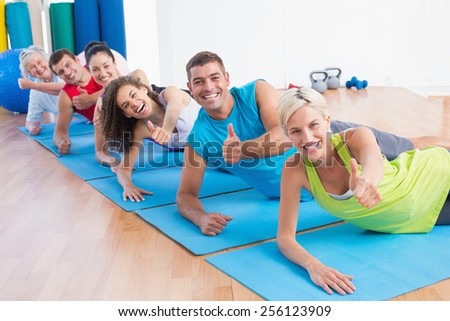 Portrait of happy people on exercise mats gesturing thumbs up at gym - stock photo