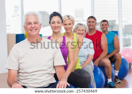 Portrait of happy people relaxing on fitness balls in gym class - stock photo