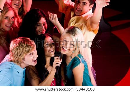 Portrait of happy people singing in microphone in the karaoke bar - stock photo
