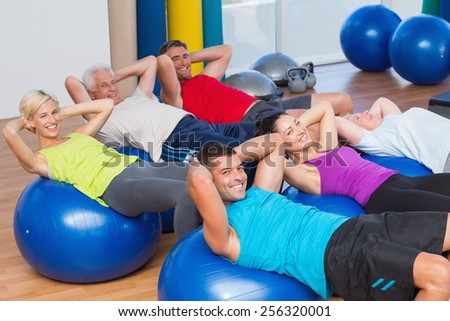 Portrait of happy people stretching on exercise balls in fitness club - stock photo