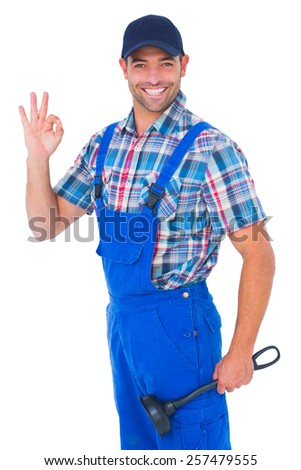 Portrait of happy plumber with plunger gesturing okay on white background - stock photo
