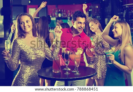 Portrait of happy positive smiling females and males having fun in the bar