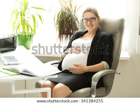 Portrait of happy pregnant businesswoman posing in chair at office - stock photo