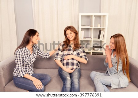 Portrait of happy pregnant woman having talk with her girlfriends - stock photo
