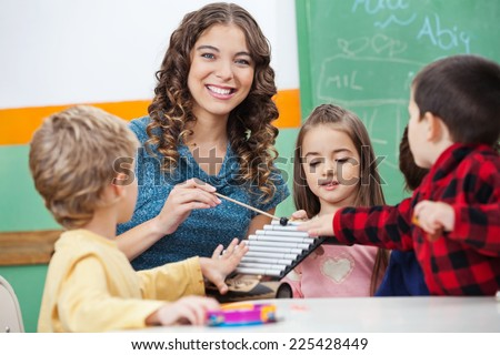Portrait of happy preschool teacher and children playing with xylophone in classroom - stock photo