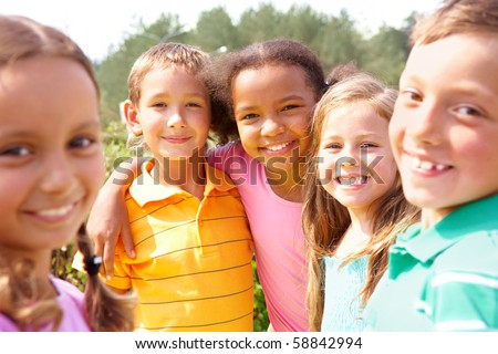 Portrait of happy preschoolers looking at camera while embracing - stock photo