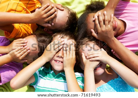Portrait of happy preschoolers lying and closing eyes by hands - stock photo