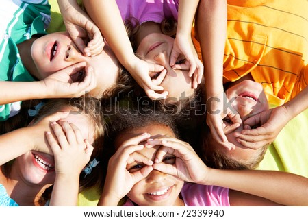 Portrait of happy preschoolers lying and looking at camera - stock photo