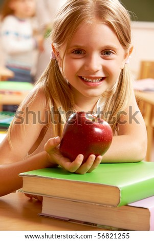 Portrait of happy pretty girl holding a red apple in the classroom - stock photo
