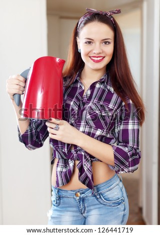 Portrait of happy pretty housewife with red  kettle at home - stock photo