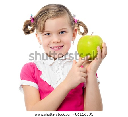 portrait of happy pretty little caucasian girl with green apple toothy smile looking at camera isolated on white studio shot pointing at apple - stock photo