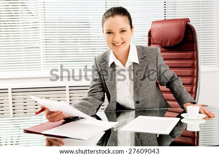 Portrait of happy professional with document in hand looking at camera with smile in office - stock photo