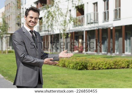 Portrait of happy real estate agent presenting office building - stock photo