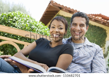 Portrait of happy relaxed couple with a book - stock photo