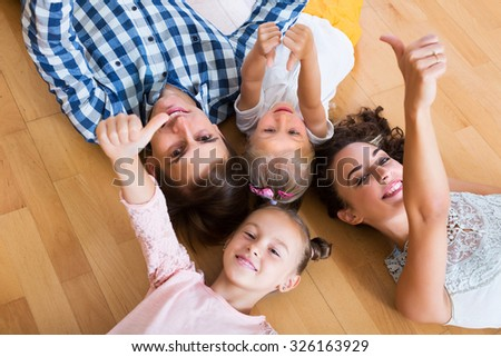 Portrait of happy relaxed family of four posing at home - stock photo