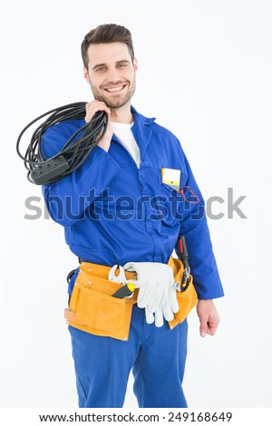 Portrait of happy repairman holding cable against white background