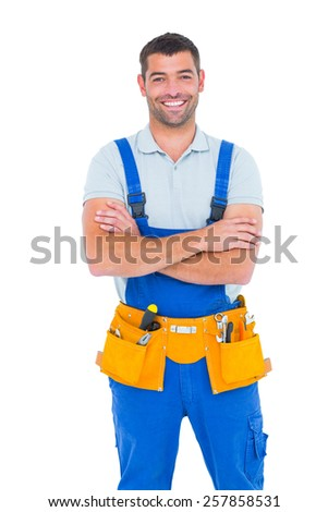 Portrait of happy repairman in overalls wearing tool belt standing arms crossed on white background - stock photo