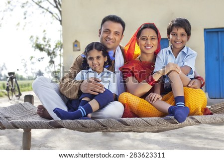 Portrait of happy rural Indian family sitting on cot - stock photo