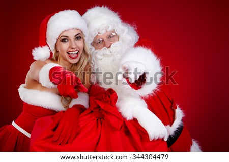 Portrait of happy Santa Claus at red studio  with his woman helper - stock photo