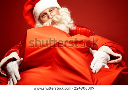 Portrait of happy Santa Claus embracing huge red sack with xmas presents - stock photo