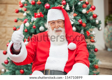 Portrait of happy Santa Claus gesturing thumbsup against Christmas tree - stock photo