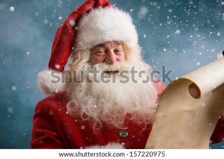 Portrait of happy Santa Claus reading Christmas letter outdoors at north pole at snowfall - stock photo