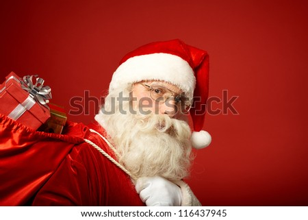 Portrait of happy Santa Claus with big red sack looking at camera - stock photo