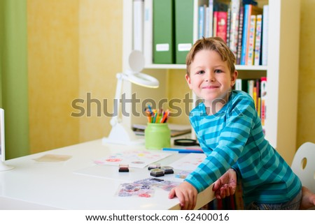 Portrait of happy school boy doing homework - stock photo