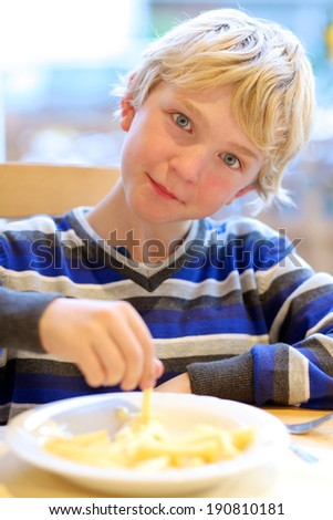 Portrait of happy school boy eating tasty french fries with mayonnaise in restaurant - stock photo