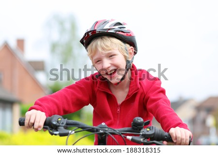 Portrait of happy school boy in safety helmet riding his bike on the street in a countryside - stock photo